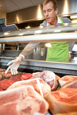 meat counter: Market assistant picking meat in the supermarket