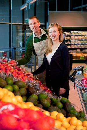 grocer: A woman buying fruit and vegetables at a supermarket, receiving help from a grocer