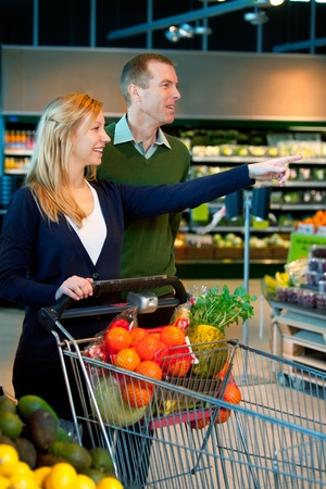 A happy couple in a supermarket buying groceries Stock Photo - 9685411