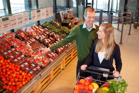 Mid adult man pointing at vegetables while shopping with wife in shopping store photo