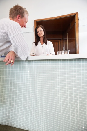 Spa receptionist with a male customer at the welcome desk photo