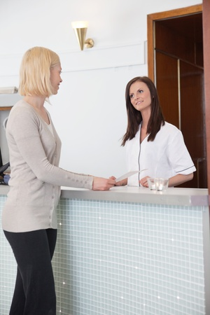 standing reception: Blond girl at the reception desk of a spa centre