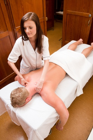A massage therapist at work, giving a massage to a male in an old style spa photo