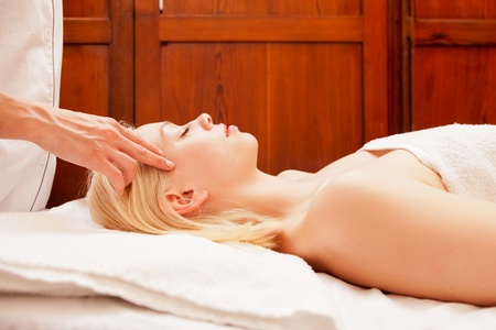 A beautiful blonde woman receiving a head and scalp massage in a spa photo
