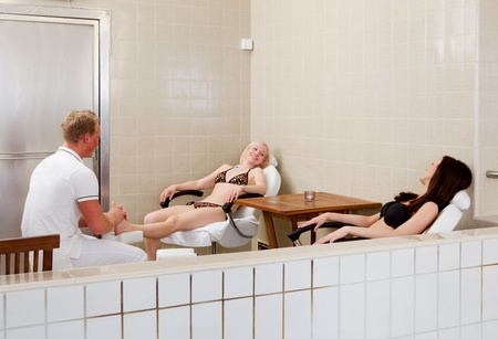 A woman receiving a foot massage with a friend in a spa photo