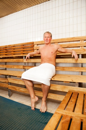 Portrait of a happy man sitting in a sauna photo