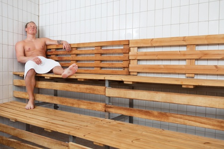 Mature man relaxing in steam room at a sauna spa photo