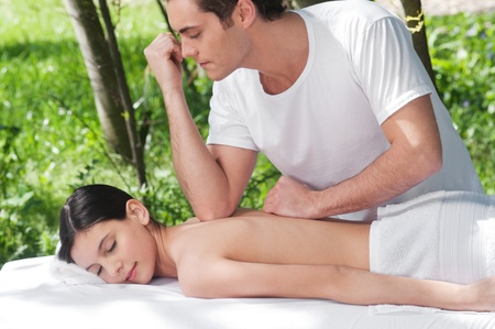Massage therapy: Young man giving massage elbow to a beautiful woman on back Stock Photo