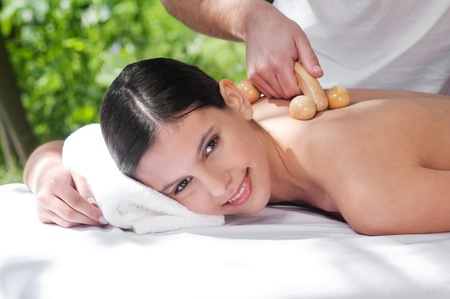Beautiful young woman getting massage by a therapist photo