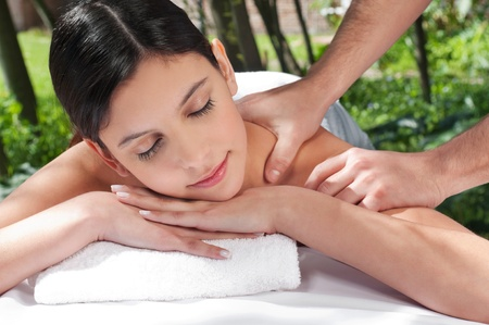 An attractive Caucasian woman getting massaged by a therapist photo
