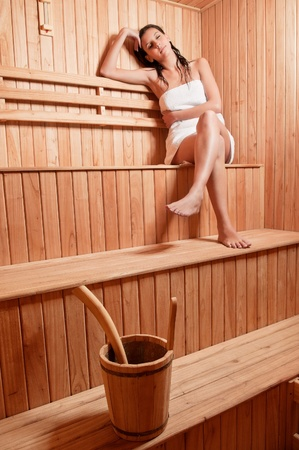Beautiful young woman relaxing in a finish sauna photo