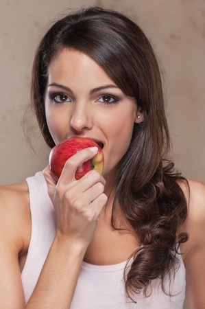 woman apple: Portrait of beautiful young woman eating an apple