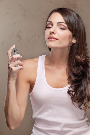 An attractive young woman applying perfume photo