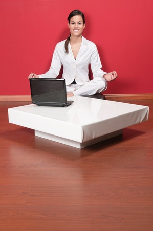Young beautiful businesswoman sitting in yoga lotus position with laptop on table photo