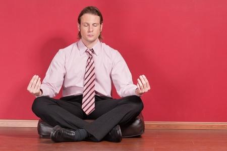 Businessman meditating in yoga lotus pose on floor photo