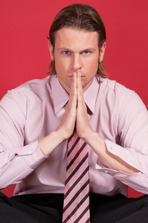 Portrait of a thoughtful businessman with hand clasped against red background photo