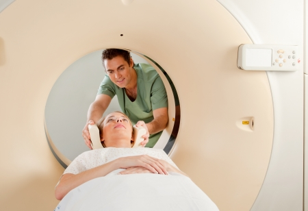 A CT Scan Technician preparing a patient for scanning photo