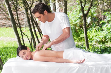 Young woman getting a massage by a handsome man Stock Photo - 9886888