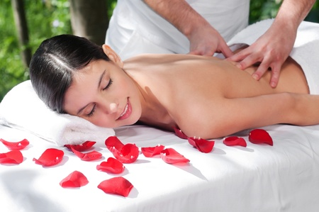 Massage therapy: Beautiful woman getting massage and spa treatment in natural setting Stock Photo