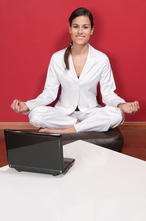 Attractive businesswoman sitting in yoga lotus position with laptop on table Stock Photo - 9887457