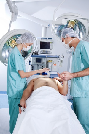 Patient being operated by the surgeons in operation theatre Stock Photo - 9887234