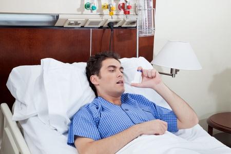 asthme: Asthmatic patient de sexe masculin sur le lit en utilisant inhalateur pour l'asthme