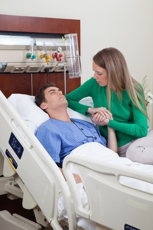 healthcare visitor: Man on a hospital bed with woman holding his hand with concern Stock Photo