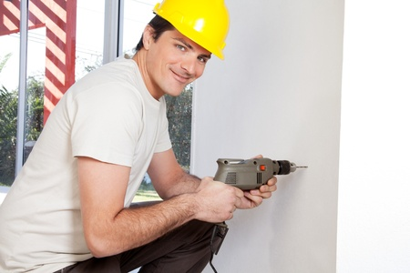 gimlet: Portrait of smiling man worker with hard hat drilling wall Stock Photo
