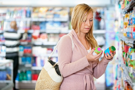 comparison: Young woman holding jar in the supermarket with people in the background Stock Photo