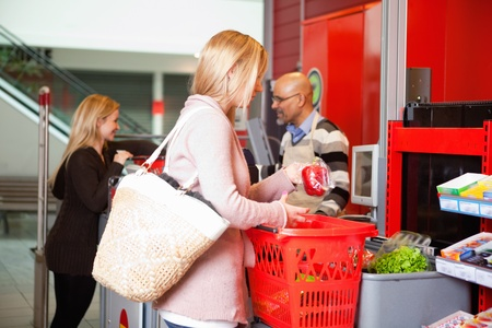 Customer shopping in supermarket with people in the background Stock Photo - 9887245