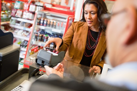 supermarket checkout: A young woman paying for grocery purchase with a mobile phone