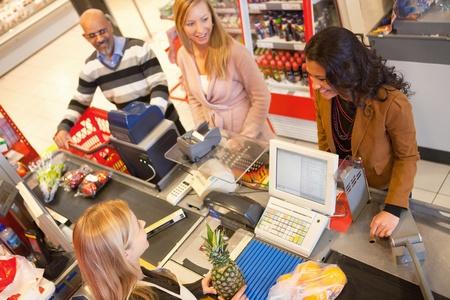 abarrotes: Vista de �ngulo alto del cajero con una fila de personas en el mostrador de check-out Foto de archivo
