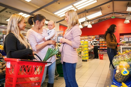 Mother carrying child with friends shopping in supermarket photo