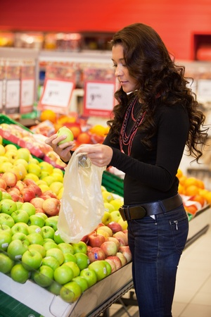 Young woman buying fruits in the supermarket photo
