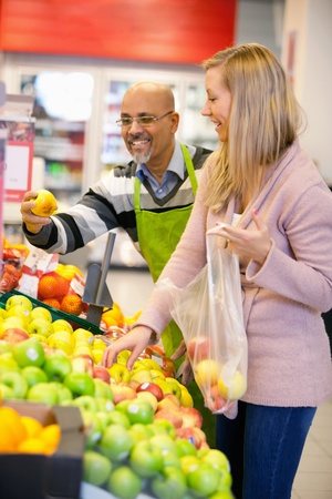 customer assistant: Happy young woman buying fruits with shop assistant in the background