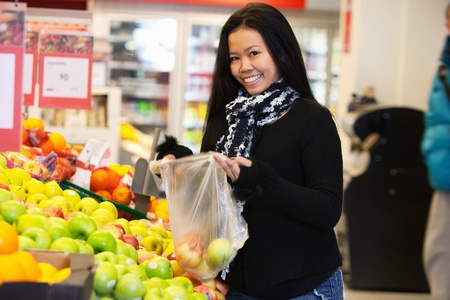 Portrait of a happy young woman buying apple in the supermarket photo