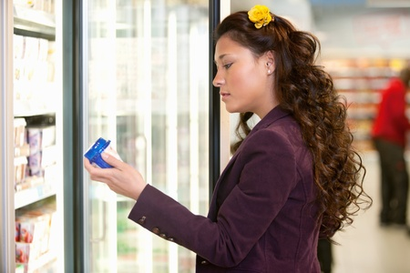 Young woman holding container in front of refrigerator in the supermarket photo