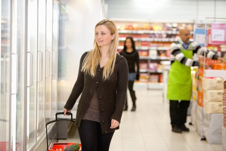 superstore: Smiling woman walking in shopping centre, looking in refrigerator with people in the background