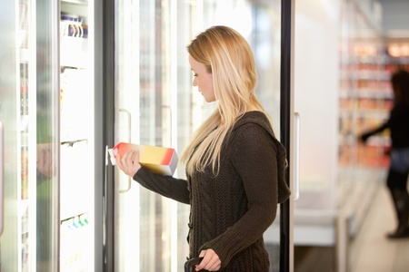 cooler: Beautiful young lady purchasing a product at a grocery store with person in the background Stock Photo