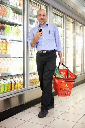 Full length of mature man in shopping store carrying basket and using mobile phone while walking photo
