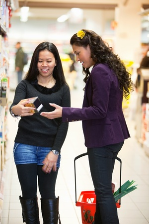 Smiling women looking at a product in a shopping store with people in the background Stock Photo - 9886874