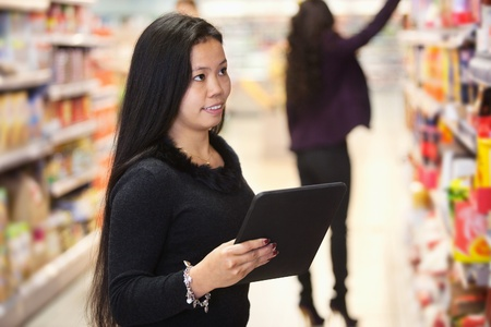 Young woman looking at the products while using digital tablet in shopping centre with person in the background photo