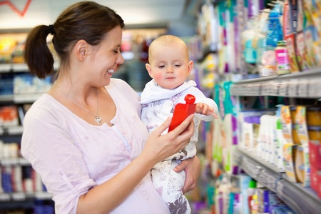 food stores: Cheerful mother playing with baby and spending time in shopping store