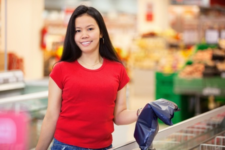 Smiling woman holding product in shopping centre and looking at camera photo