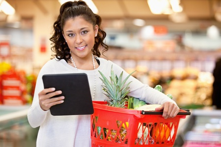 superstore: Woman with digital tablet holding fruit basket in shopping centre and looking at camera Stock Photo