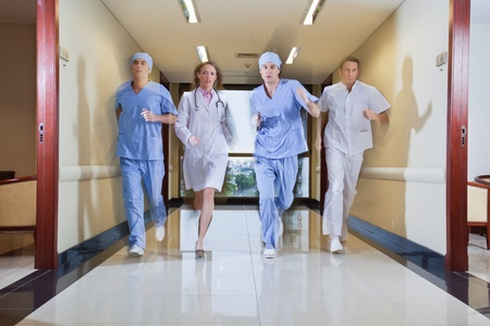 Team of surgeon and nurse running in hallway of hospital photo