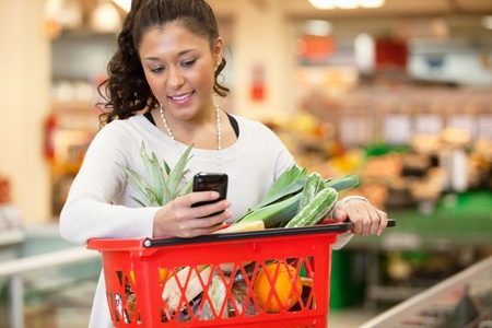 grocery trade: Smiling young woman using mobile phone while shopping in shopping store