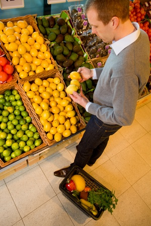A male in a grocery store buying lemons - sharp focus on lemons photo