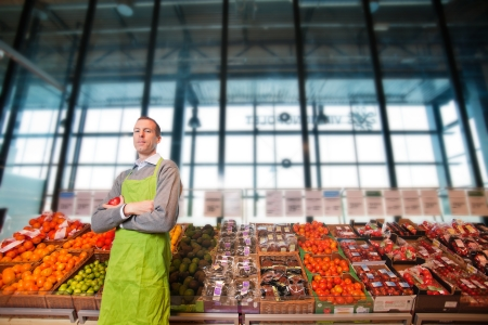 Portrait of a grocery store clkerk or owner in front of a vegetable counter photo