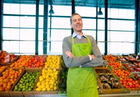 A grocery store owner standing in front of vegetables and fruit photo